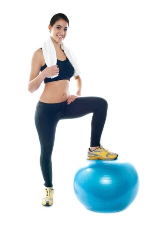 Beautiful young woman posing with one leg on fitness ball photo