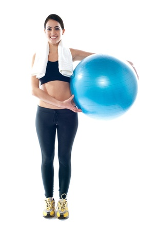 Attractive sporty teenager posing with fitness ball beside her waist photo