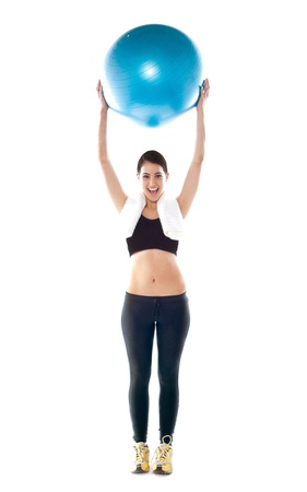 Gorgeous fit lady holding pilate ball over her head isolated against white background photo