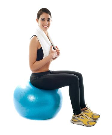 Female fitness trainer sitting on ball isolated against white background photo