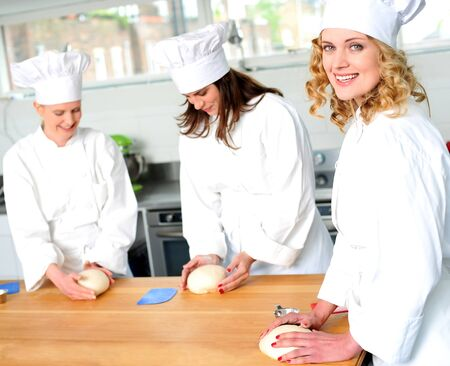 Female chefs at work in a restaurant kitchen. Kneading dough photo