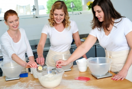 woman cooking: Female chefs team collecting flour from bowl for preparing something
