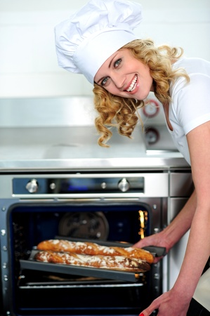 Female chef taking out baguette from oven. Bent down photo