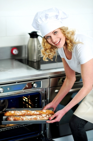 Caucasian female chef putting baguette into microwave oven photo