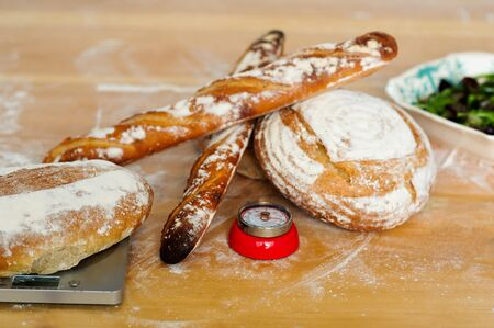 Baguettes and breads on wooden table. Closeup shot photo