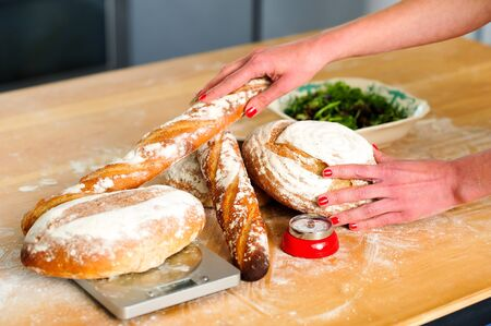 Females hands arranging baguettes and breads. Closeup image photo