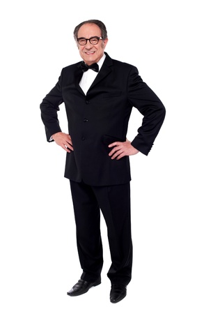 standing man: Studio shot of a stylish old man standing with hands on his waist