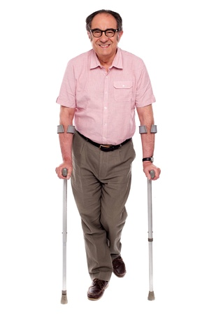 paralyzed: Smiling senior man walking with two crutches. All on white background