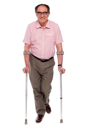 Smiling senior man walking with two crutches. All on white background photo