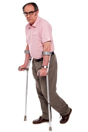 Depressed senior male standing with two crutches isolated over white