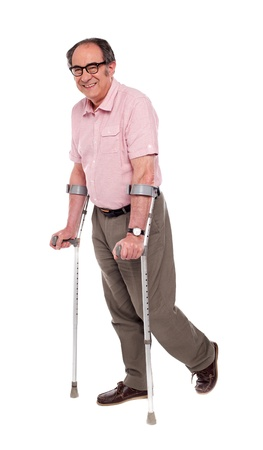Smiling elderly man with crutches over white background photo