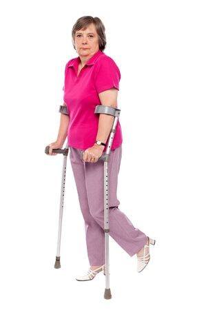 Unhappy handicapped woman with crutches. Looking at camera photo