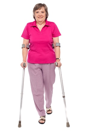 Full length portrait of an injured senior woman isolated over white background photo