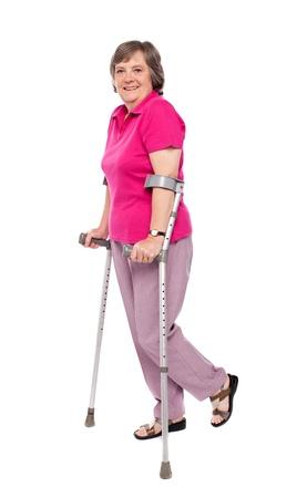 Smiling senior woman walking with crutches. All on white background photo