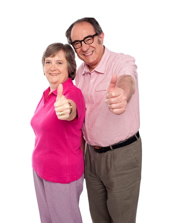 Senior couple gesturing thumbs up towards camera, isolated photo