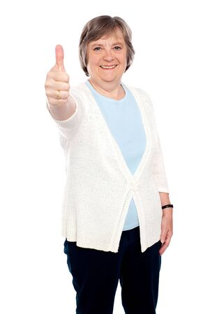 posing  agree: Smiling old lady showing thumbs up gesture to camera. Isolated on white