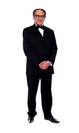 Attractive senior man posing in tuxedo isolated over white background photo