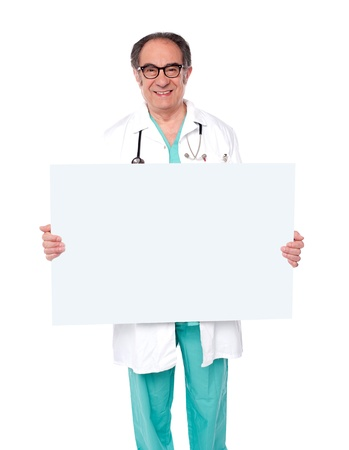 Aged male doctor posing with white blank billboard in front of camera photo