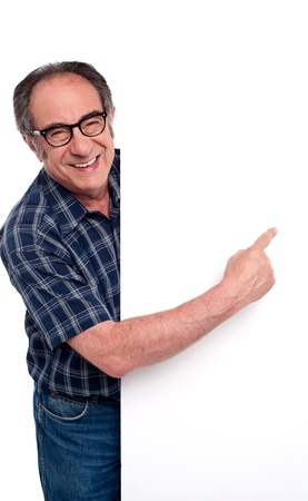 Causal matured man pointing finger at placard isolated over white background photo