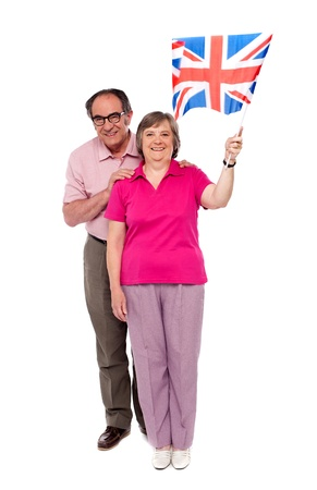 Old couple waving UK flag. Supporting nation and cheering photo