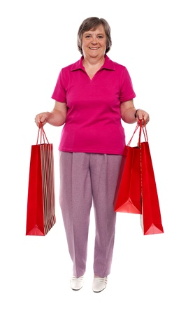Smiling woman holding shopping bags isolated against white background Stock Photo - 14301635