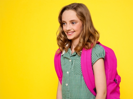 School girl with backpack against yellow background photo