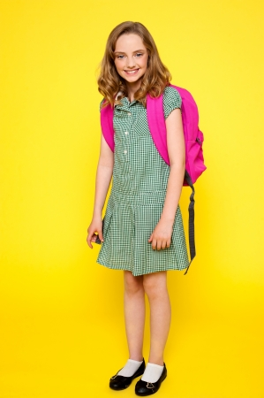 Full length portrait of cheerful school girl standing over yellow background
