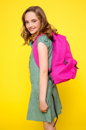 Pretty school girl carrying pink backpack and looking at camera photo