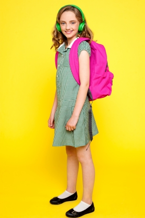 Portrait of a school girl wearing headphones and carrying school bag photo