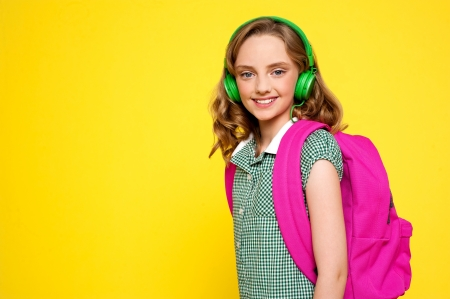 Smiling girl posing with headphone and bag isolated over yellow photo