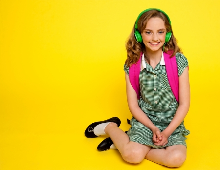 Pretty girl kid listening to music. Seated on floor. All on yellow background