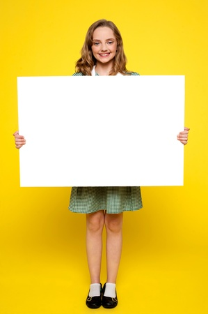 Teenager showing white blank billboard isolated against yellow background photo