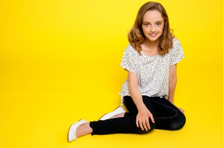 Trendy young fashionable girl sitting in style isolated over yellow background Stock Photo - 14337031