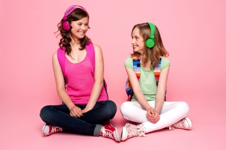 Seated beautiful teenagers looking at each other. Pretty schoolgirls photo