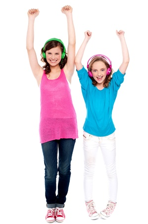 Excited young girls enjoying music together isolated over white. Full length portraits photo