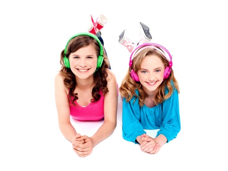 Two beautiful girls lying on floor wearing headphones and enjoying music photo