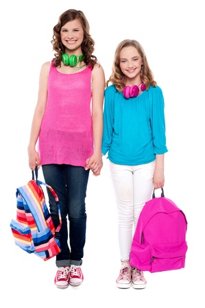 Best friends standing hand in hand and smiling at camera. Holding school bags photo
