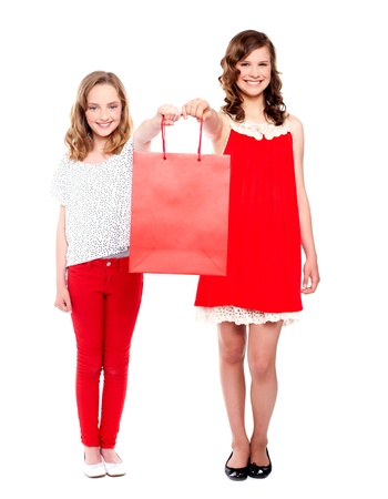 Full length portrait of beautiful teenagers holding shopping bag photo