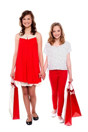 Glamorous girls walking after purchases against white background photo