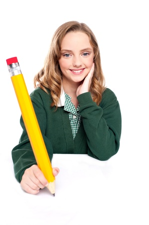 over sized: Young girl using an over sized pencil. Writing on surface