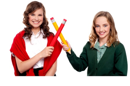 over sized: Smiling teenagers making cross sign with over sized pencils. All on white background Stock Photo