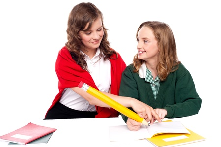 Girl explaining solution to her friend and helping her resolve question photo