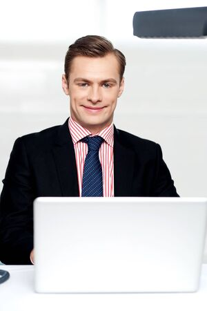 Attractive smiling man operating a laptop isolated against white background Stock Photo - 14382583