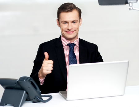 Cheerful businessperson gesturing thumbs up to camera while working in office Stock Photo - 14382553