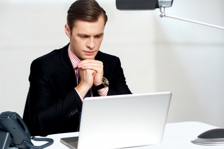 Seus businessman in office concentrating on laptop with hands resting on chin Stock Photo - 14382587
