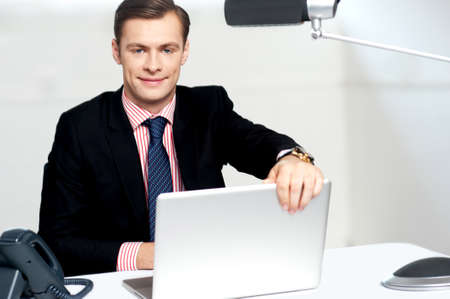 shut down: Young happy businessman holding laptop about to shut it down. Lets call it a day