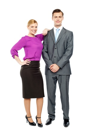 attire: Business team members posing together. Woman resting hands on young businessman
