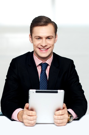 enabled: Cheerful male executive holding touch screen enabled digital device Stock Photo