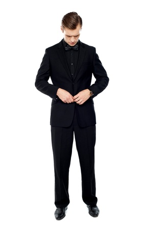 Retrato de cuerpo entero de caballero apuesto y joven metiendo el botón de la chaqueta Foto de archivo