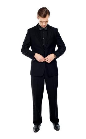 naar beneden kijken: Volledige lengte portret van knappe jonge man stopte zijn jas knop